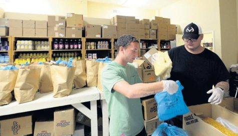 Wesley Dawson, left, and Preston Evans bag bread for sacks of groceries to be given to clients at Loaves and Fishes. Screened clients receive over 3,000 bags of food every year in the program