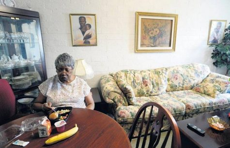 Barbara Hatcher, who lives alone in McAfee Towers, enjoys a lunch at her apartment brought by a Meals on Wheels staffer. Hatcher says the human contact is at least as nutritious as the crab salad, fruit and chocolate milk meal.