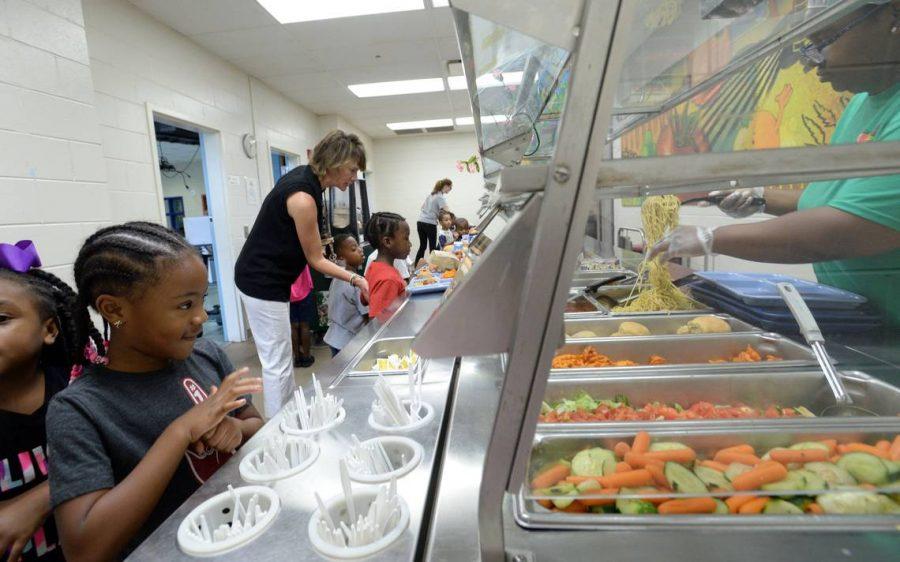 Alexander II Magnet School kindergartener Rylee Davis, left, says she loves spaghetti as she goes through the lunch line.