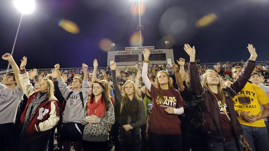 Students sway their arms as a praise band with Central Baptist Church in Warner Robins performs during a 2012 Fellowship of Christian Athletes Fields of Faith event at Perry High School's Herb St. John stadium.