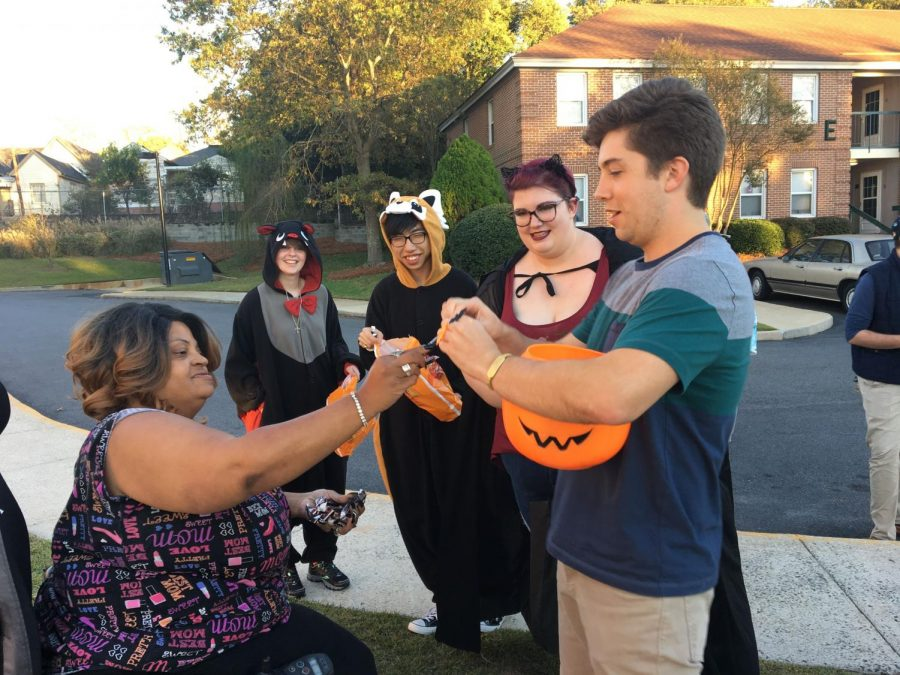 A resident of St. Paul Apartments gives candy to ELF members to thank them for their reverse trick-or-treat event.