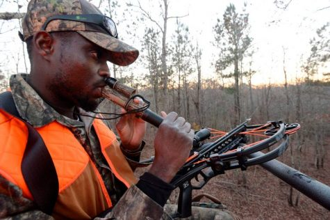 Edwin Pierre-Lewis, a native of Haiti who attends graduate school at the University of Georgia, uses a buck call as he hunts deer west of Athens. He learned to hunt as part of the Field to Fork program and has become a mentor, now teaching others how to hunt.