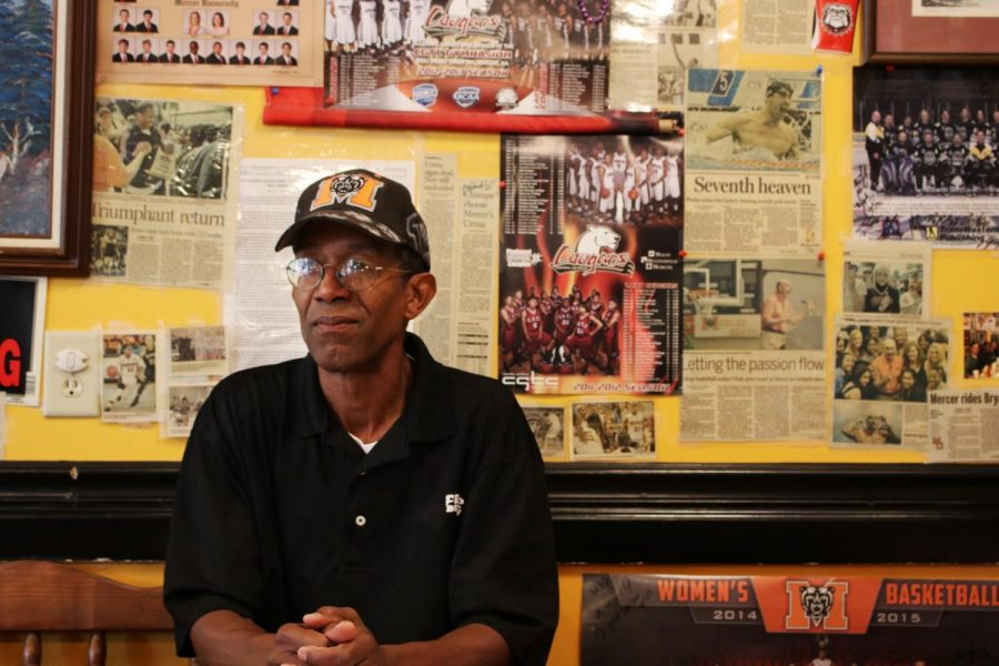 Carl Fambro sitting in front of one of his Mercer University memorabilia filled walls. His favorite part about owning a restaurant is the community involvement and connecting the people of Mercer Village with his chicken wings.