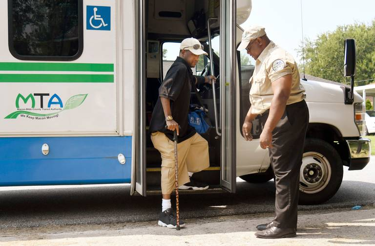 Macon, GA, 08/14/2018: Macon Transit Authority driver Charlie Huff watches over as Donald Wade exits a paratransit bus at his home in West Bibb County August 14, 2018, after receiving dialysis at a center in downtown Macon.