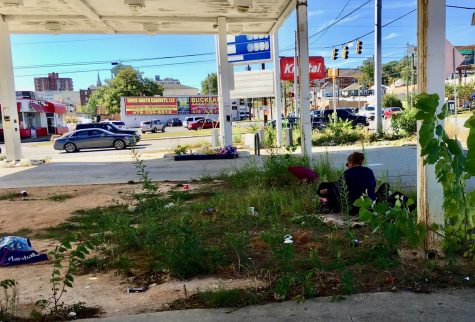 A woman sifts through a suitcase Wednesday at an abandoned convenience store property at the corner of Spring Street and Riverside  Drive.