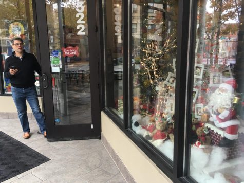 Travis Jean Emporium owner Scott Mitchell looks at his decorated window on Cherry Street as downtown prepares for the holidays.