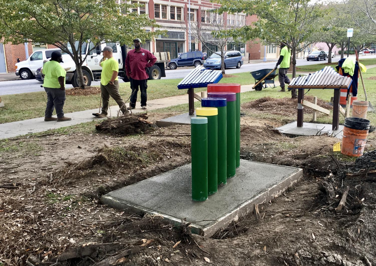 Macon-Bibb County employees install  two xylophones and a set of bongo drums Monday in Turpin Park's new Music Sculpture Park on Third Street near Poplar.