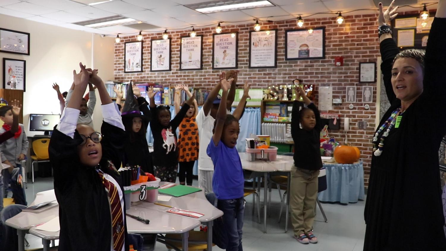 Maria Andrade, executive director of On the Same Breath, leads a group of Alex II Magnet School third graders through four minutes of breathing exercises.
