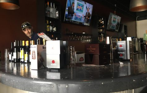 Miramar Raw Bar & Tapas bar manager Josh Howard stocks liquor at the new restaurant that is opening Feb. 13 on Forsyth Road in North Macon.