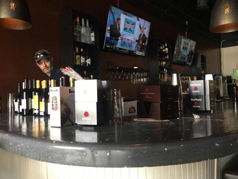 Miramar Raw Bar & Tapas bar manager Josh Howard stocks liquor at the new restaurant that is opening Feb. 13 on Forsyth Road in North Macon.