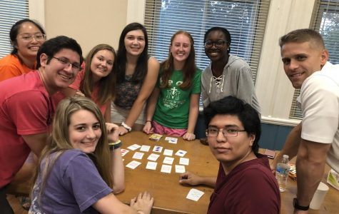 A group of members of Mercer's Catholic Campus Ministry enjoy each other's company as they play a card game at their first meeting of the year in August 2019.