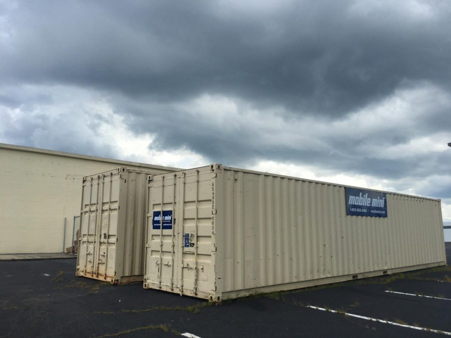 Two rented shipping containers behind the Macon-Bibb County Board of Elections represent just one of the added expenses for the state's new voting machines.