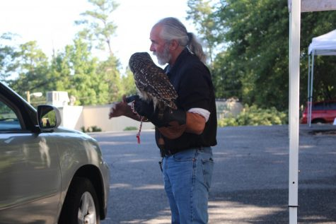 A man with a gray ponytail and light skin stands beside a vehicle. There is a large barn owl on his arm.