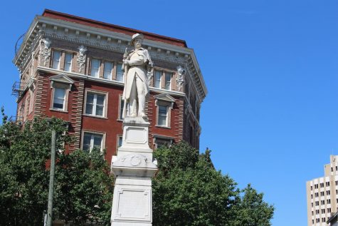 An image of Macon's Confederate Monument. He is a man made of white marble standing on a tall white marble platform and holding a rifle. Behind him is a tall brown buildin, green trees and a clear blue sky.