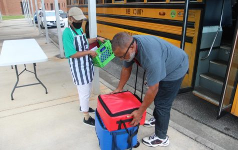 Bus driver Michael Huff and cashier Barbara Blair load meals onto a school bus at Burdell-Hunt Magnet Elementary School.