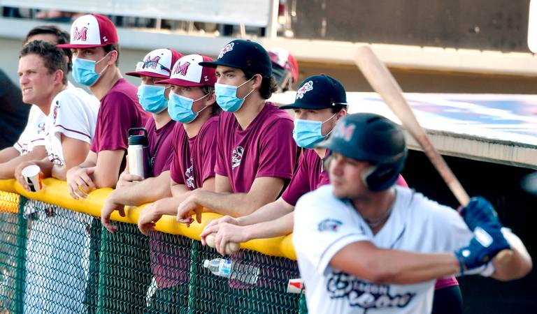 Macon Bacon players watch an intrasquad scrimmage from the first base dugout Monday night. The Bacon's home opener is Thursday against Savannah. The team is reducing attendance capacity from 3,300 to roughly 1,300 seats to adhere to social distancing guidelines. JASON VORHEES JVORHEES@MACON.COM