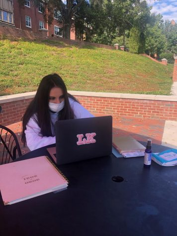 Mercer International student, Lucia Guiterrez, sits outside on campus working on an assignment.