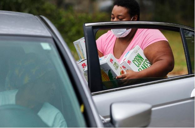 Volunteer Kenya Hampton loads groceries in the back of a recipient's car. According to the group Feeding American, just under half of the people accessing food aid during the COVID-19 recession are doing so for the first time in their lives.