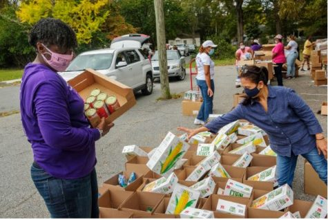 Volunteers, mostly from the Single Moms Connect support group, prepare grocery boxes during one of the group