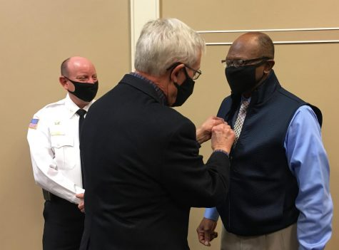 Retired Macon-Bibb fire chief Marvin Riggins, right, receives an honorary Kiwanis Club pin from Bob McDuffie as acting Chief Shane Edwards looks on.