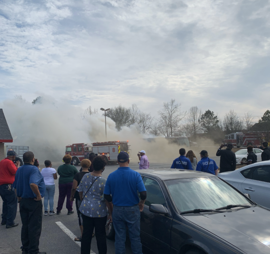 Smoke bellowing out of the burning Mercer bus, flows across the parking lot at a South Carolina Golden Corral.