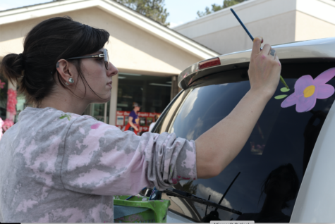 Kelly Walker, seen here in Macon painting flowers on the window of a car, continues a long Cherry Blossom tradition. Walker carry on the learned art of Cherry Blossom painting that was started by her mother, Peggy Whyte.
