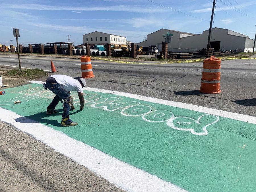 A Bike Walk Macon volunteer paints a logo for Greenwood Bottoms on Bay Street in Macon, Ga. Feb. 27.