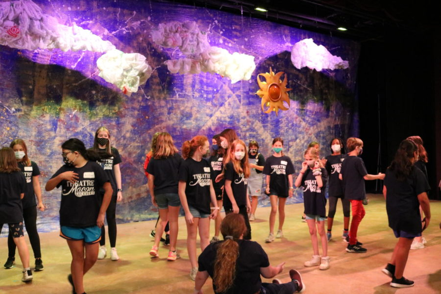 A group of students standing on stage as they practice sound and lighting design at Theatre Macon Academy summer camp.