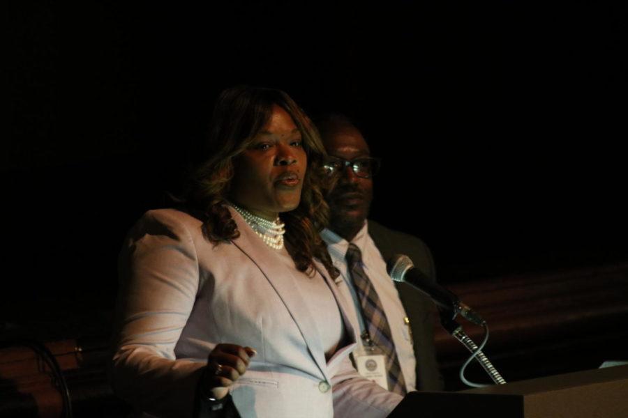 Anita Howard speaking at the podium next to Aubrey Evans during her