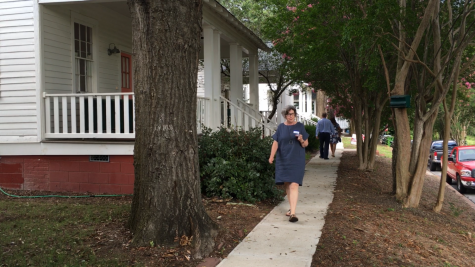 Mill Hill East Macon Arts Village resident Cassie Bryant walks to a reception after showing Mayor Lester Miller her home last month.