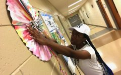 Serenity Wright hangs her artwork and handmade decorations Monday in the hall of the Bloomfield Recreation Center at 1931 Rocky Creek Road.