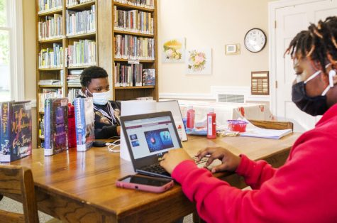 """Siblings Quinyonna Tooks, right, and Charles Knott do their schoolwork in the Oglethorpe Library in Macon County. Charles is not a fan of remote learning. """"I dont like it,"""" he said. """"In school is better for me. I can focus in there with the teachers."""""""