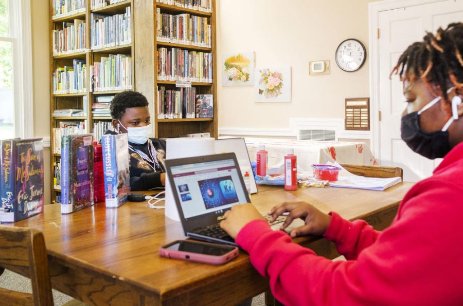 """Siblings Quinyonna Tooks, right, and Charles Knott do their schoolwork in the Oglethorpe Library in Macon County. Charles is not a fan of remote learning. """"I don"""